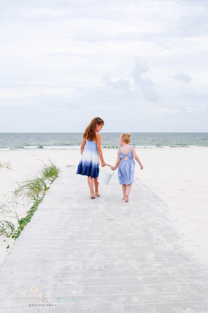 Two young sisters walking down the boardwalk holding a bucket at Johnsons Beach in Perdido Key Florida