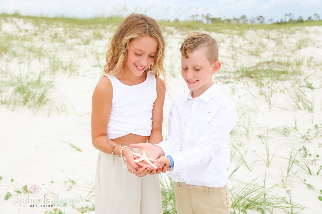 Brother and sister holding a starfish in their hands with the sand dunes behind them at Johnsons Beach in Perdido Key Florida
