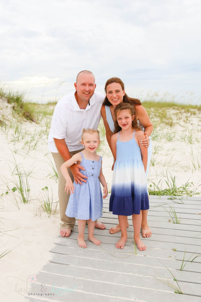 Mom and Dad standing with their daughters on a washed up boardwalk at Johnsons Beach in Perdido Key Florida