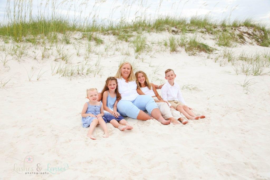 Grandma with her four grandchildren sitting in the sand at Johnsons Beach in Perdido Key Florida