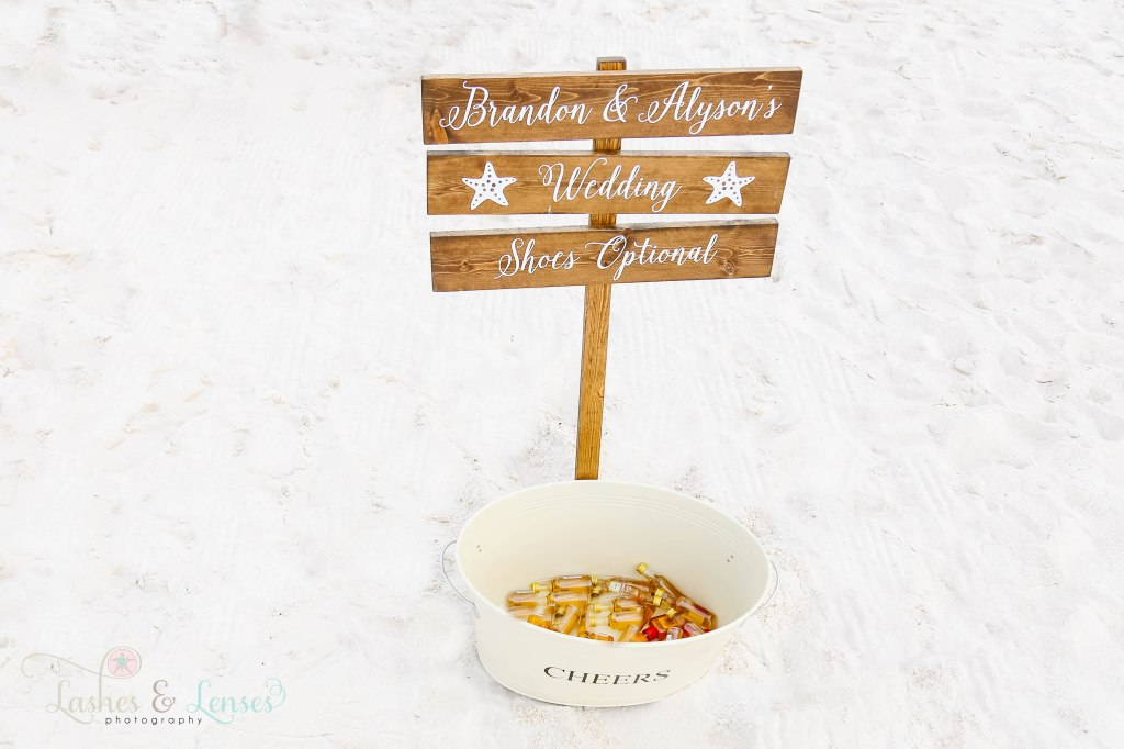 Photo of Wedding sign that says Shoes Optional and a bucket holding mini bottle of alcohol at Johnsons Beach in Perdido Key Florida