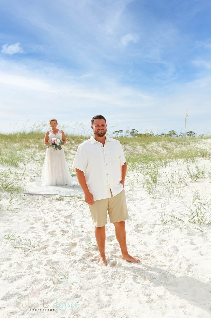 Bride behind the groom getting ready for a first look on the beach