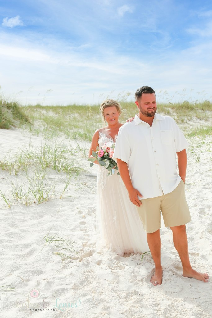 Bride tapping groom on the shoulder in the sand dunes for a first look at Johnsons Beach in Perdido Key Florida