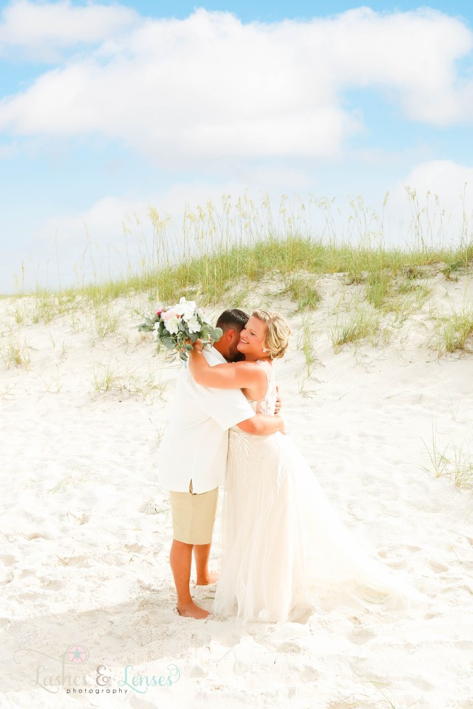 Groom and Bride hugging with the sand dunes behind them at Johnsons Beach in Perdido Key Florida