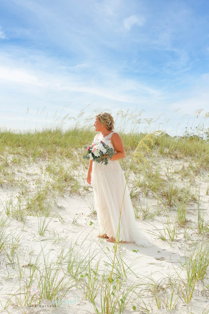 Bride in the middle of the golden sea oats at Johnsons Beach in Perdido Key Florida