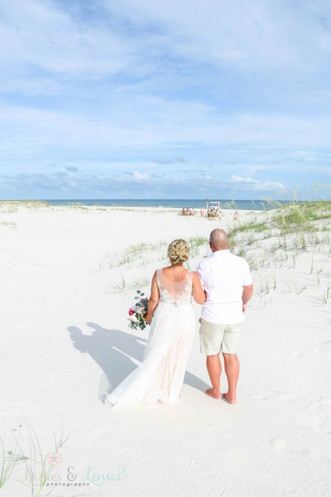Dad and Bride walking through the sand and heading towards the aisle at Johnsons Beach in Perdido Key Florida