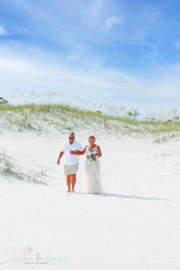 Seeing the Bride and her father as they walk through the sand and head towards the ceremony at Johnsons Beach in Perdido Key Florida