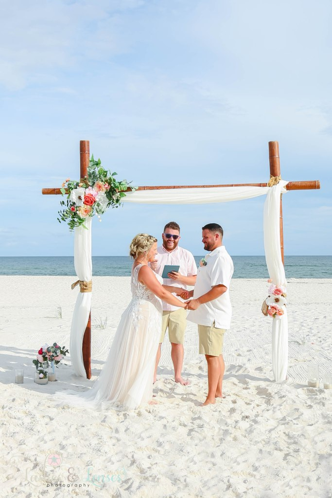 Photo of Bride and Groom with the wedding arch behind them and their brother officiating at Johnsons Beach in Perdido Key Florida