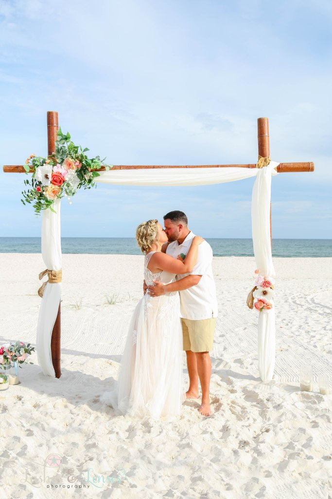 Husband and wife kissing as their marriage is sealed at Johnsons Beach in Perdido Key Florida