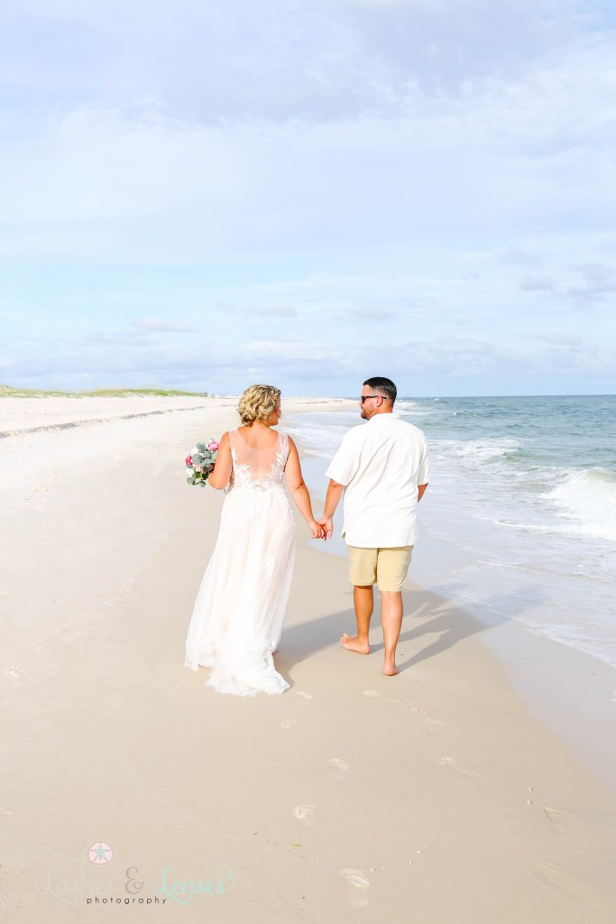 New Husband and wife walking down by the water and holding hands with their back to the camera at Johnsons Beach in Perdido Key Florida