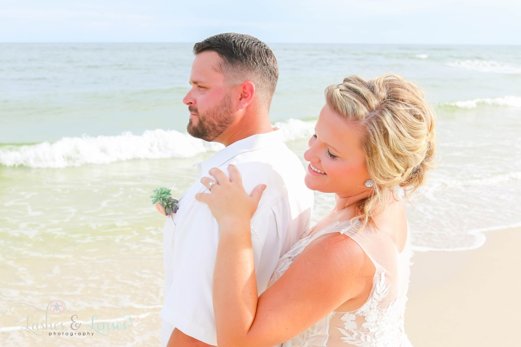 Close up of new husband and wife with the waves crashing behind them at Johnsons Beach in Perdido Key Florida