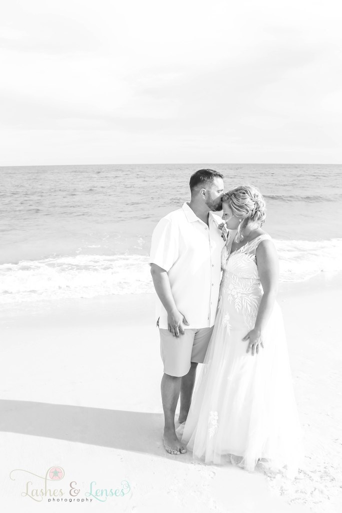 Black and white photo of husband kissing his new wife on the head and standing by the waters edge at Johnsons Beach in Perdido Key Florida
