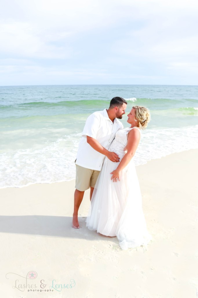 Husband dipping his new wife and going in for a kiss with the waves crashing behind them at Johnsons Beach in Perdido Key Florida