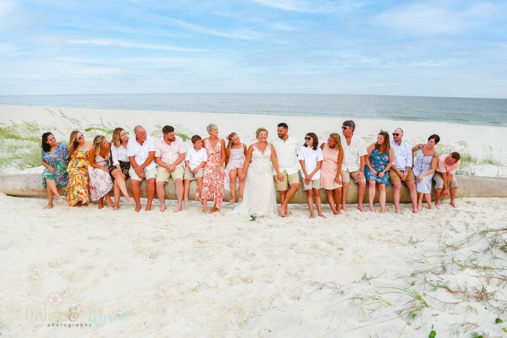 Entire Wedding party sitting on a washed up palm tree with the gulf waters behind them at Johnsons Beach in Perdido Key Florida