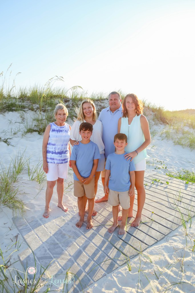Grandma, Mom, Dad and daughter as well as two sons standing on a washed up boardwalk at Johnsons Beach in Perdido Key Florida