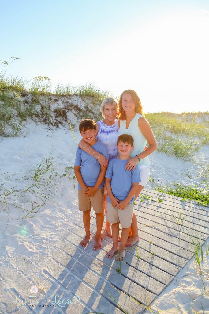Grandma with her granddaughter and two grandsons standing on a boardwalk at Johnsons Beach in Perdido Key Florida