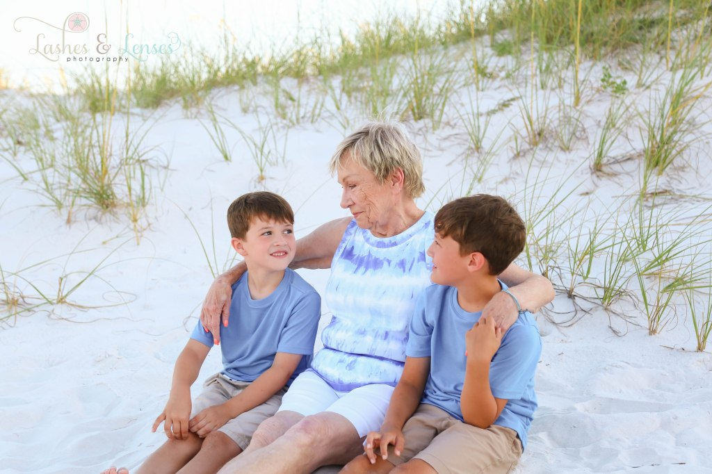 Grandma sitting in the sand with her grandsons and looking at them at Johnsons Beach in Perdido Key Florida