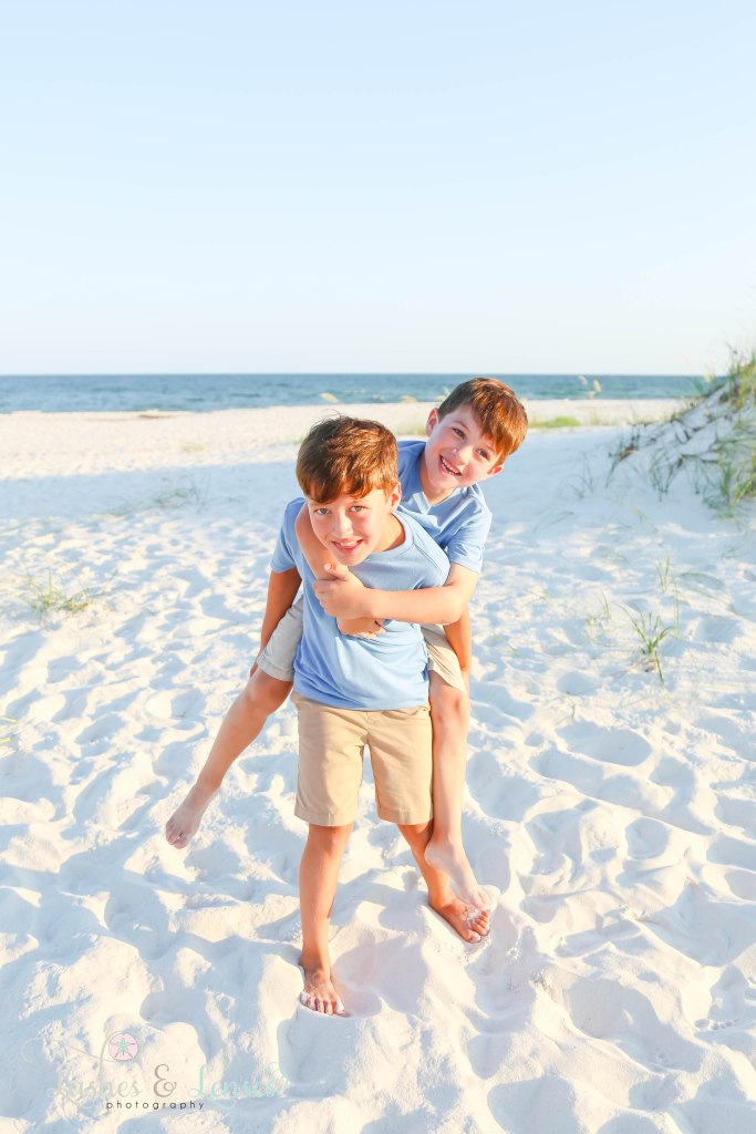 Younger brother on older brothers back with the gulf behind them at Johnsons Beach in Perdido Key Florida