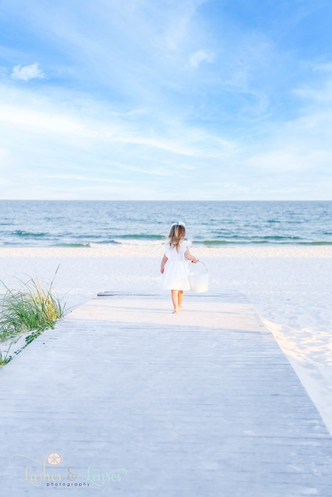 Little girl in white dress and big white bow walking down the boardwalk with a bucket in her hand at Johnsons Beach in Perdido Key Florida
