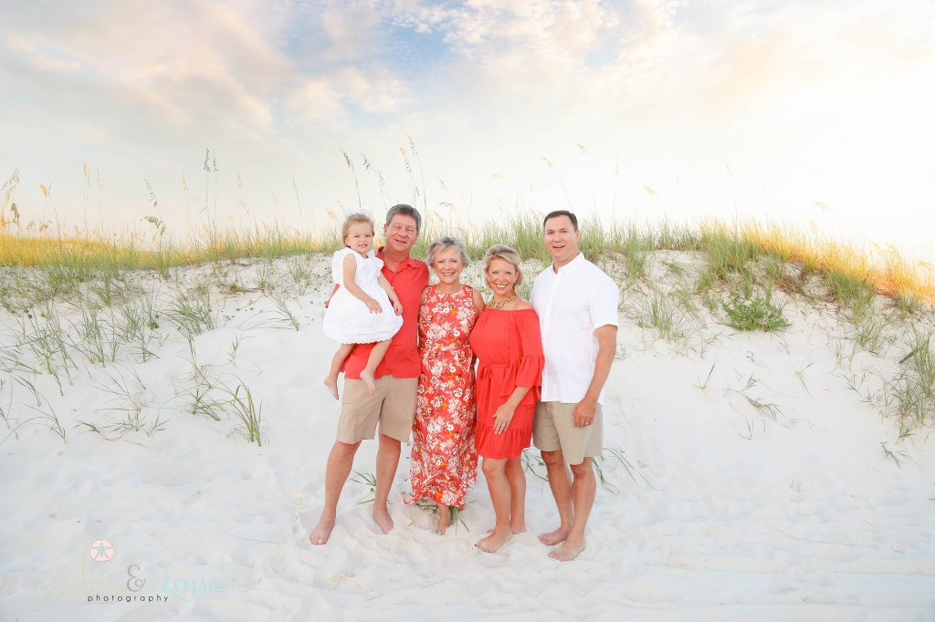 Grandparents, Mom and Dad and daughter standing next to big sand dunes v