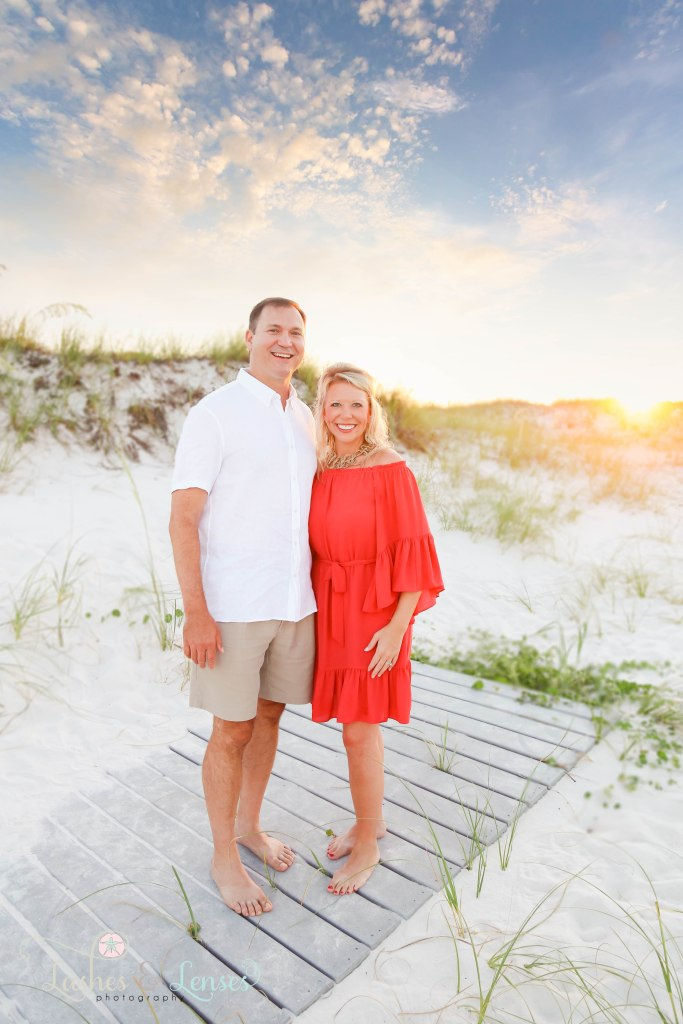 Husband and Wife standing on a washed up boardwalk at Johnsons Beach in Perdido Key Florida