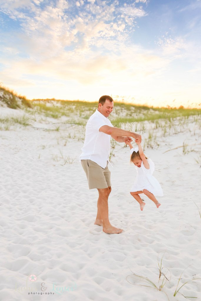 Dad twirling his toddler daughter around surrounded by sand dunes at Johnsons Beach in Perdido Key Florida