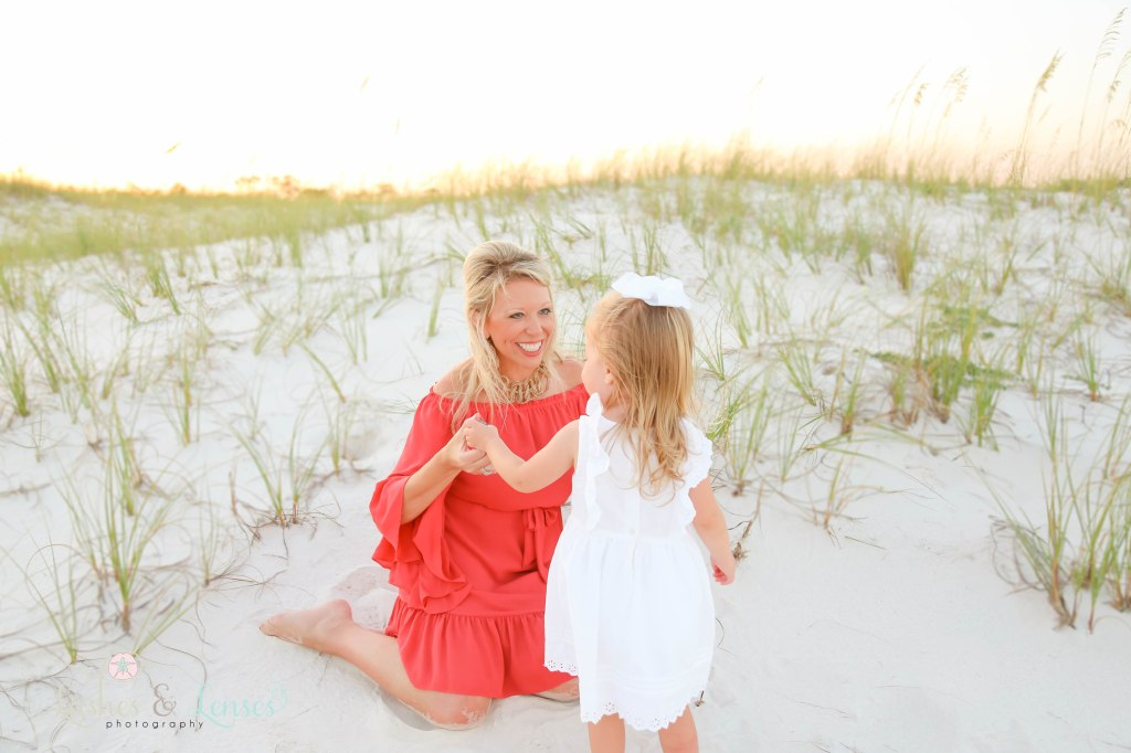 Mom sitting in the sand and talking with her daughter at Johnsons Beach in Perdido Key Florida