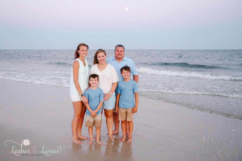 Mom, Dad and their three children standing down by the waters edge with the full moon behind them at Johnsons Beach in Perdido Key Florida