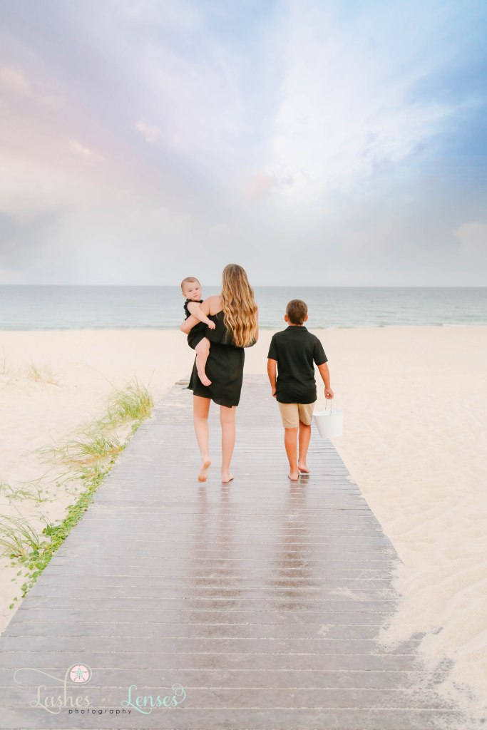 Older sister holding baby sister and walking with their brother down the boardwalk towards the water at Johnsons Beach in Perdido Key Florida