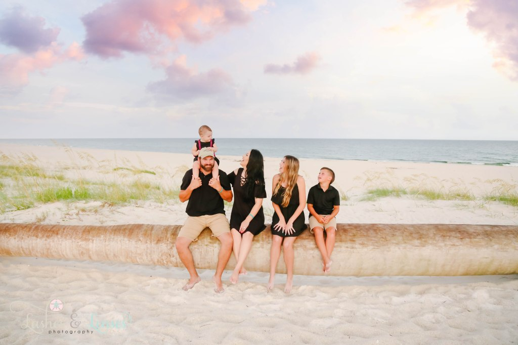 Family of mom, dad, older sister, brother and baby sister sitting on a washed up palm tree with the water behind them at Johnsons Beach in Perdido Key Florida