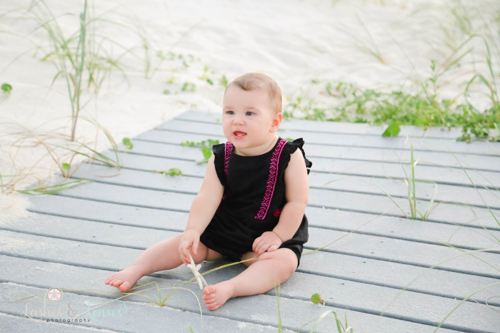 Baby girl sitting on a washed up boardwalk and holding a starfish at Johnsons Beach in Perdido Key Florida