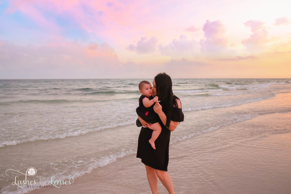 Mom kissing baby girl on the cheek with the water and colorful sunset behind them at Johnsons Beach in Perdido Key Florida