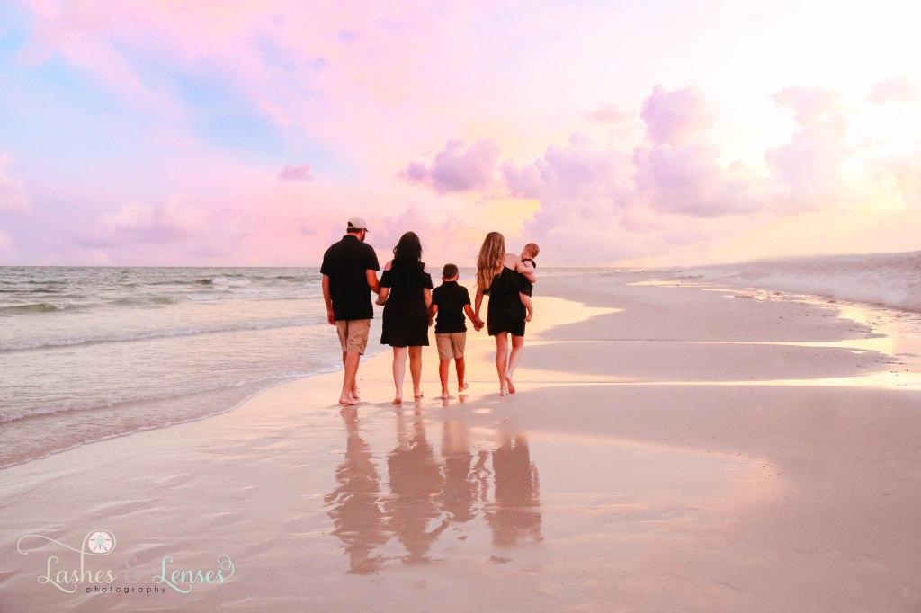 Family walking hand in hand down the beach at Johnsons Beach in Perdido Key Florida