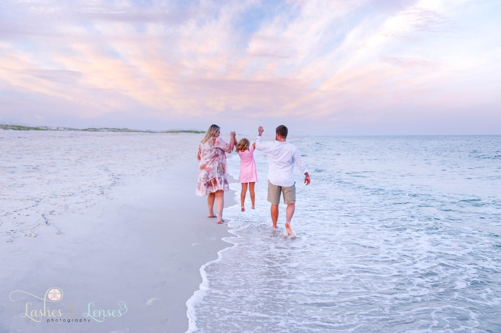 Mom and Dad swinging their daughter in the air in between them and walking along the shores edge at Johnsons Beach in Perdido Key Florida