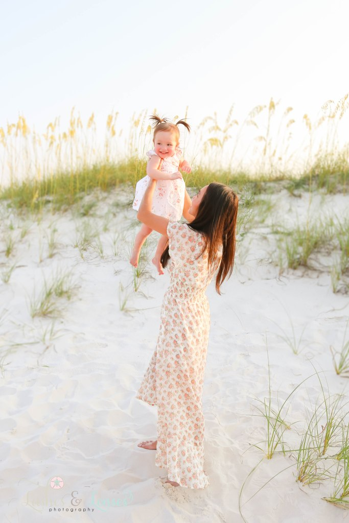 Mom racing toddler daughter above her head with the sand dunes and sea oats behind them at Johnsons Beach in Perdido Key Florida