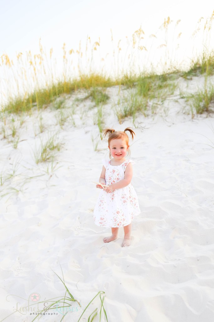 Little girl holding a starfish in her hands with the sand dunes and sea oats behind her at Johnsons Beach in Perdido Key Florida