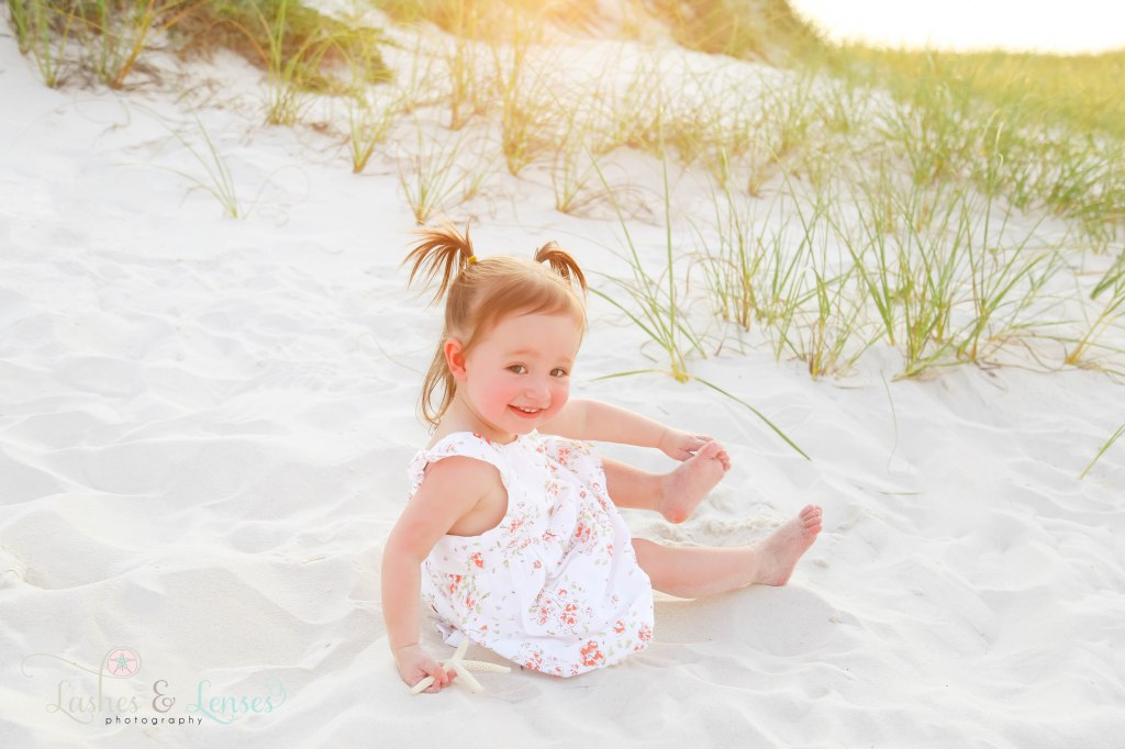 Close up photo with little girls sitting in the sand at Johnsons Beach in Perdido Key Florida