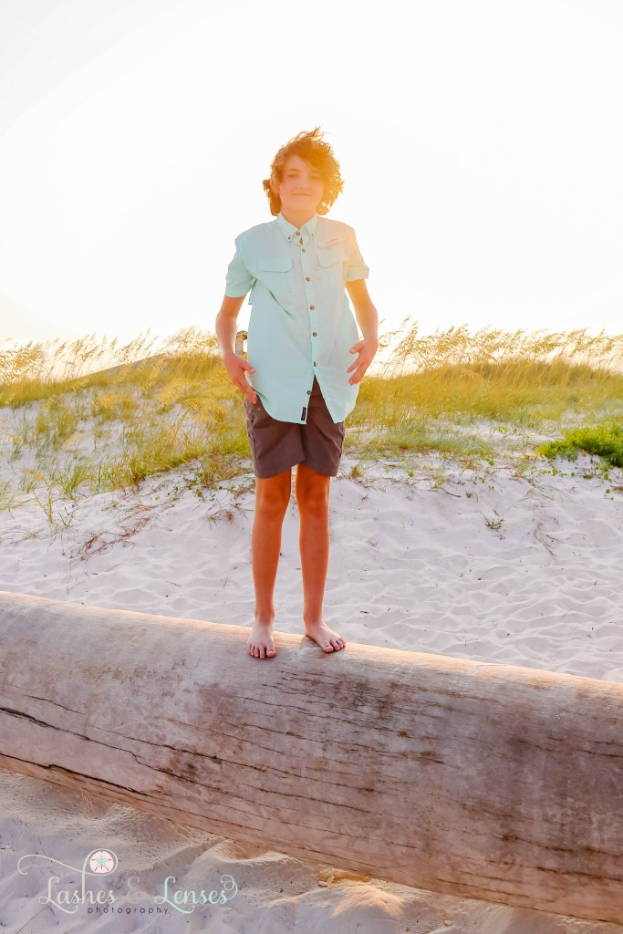 Teen Boy standing on top of a washed up palm tree at Johnsons Beach in Perdido Key Florida