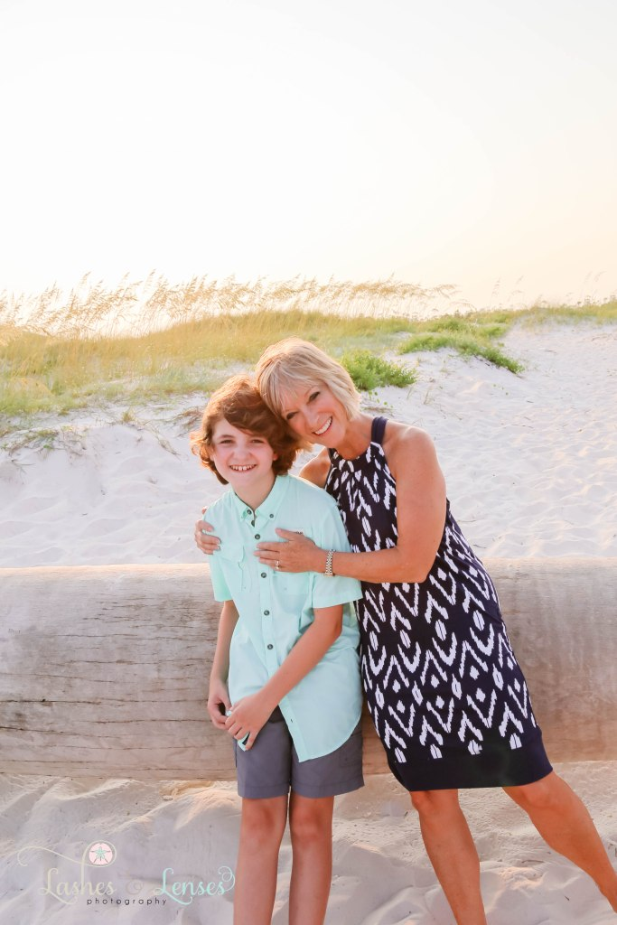 Grandma and grandson hugging while leaning against a washed up palm tree at Johnsons Beach in Perdido Key Florida