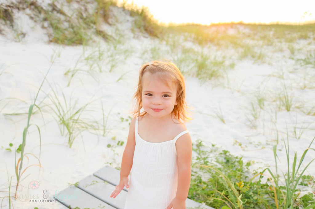 Close up photo of toddler girl with the sand dunes behind her at Johnsons Beach in Perdido Key Florida