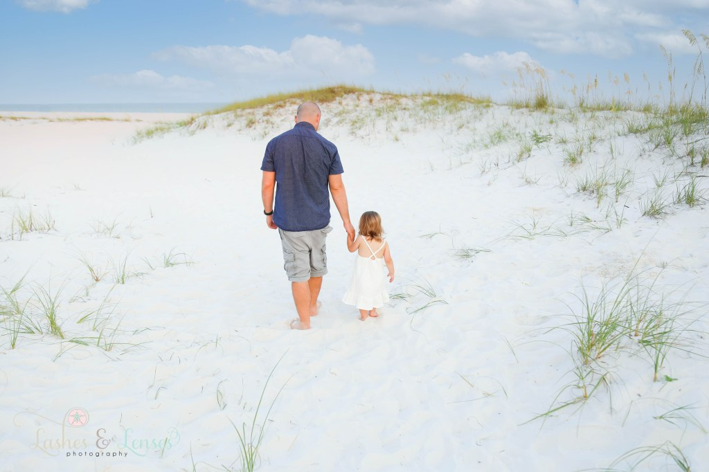 Dad and toddler daughter walking hand in hand towards the water and sand dunes at Johnsons Beach in Perdido Key Florida