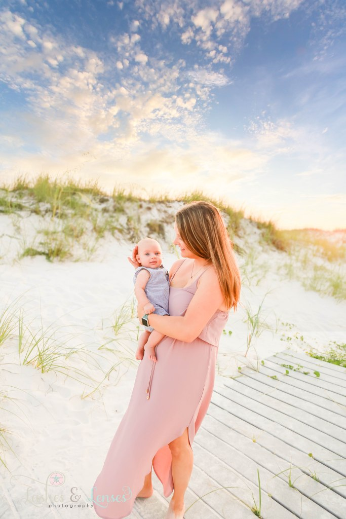 Mom holding four month old son and smiling down at the baby, baby boy looking right at the camera at Johnsons Beach in Perdido Key Florida