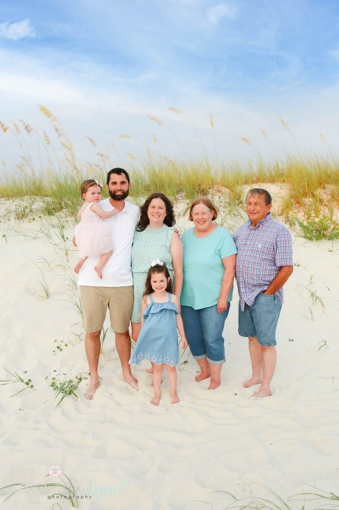 Grandparents, Mom and Dad and two daughters standing in front sand dunes at Johnsons Beach in Perdido Key Florida