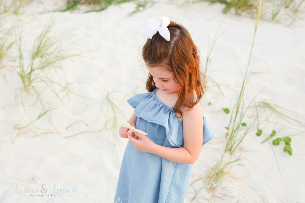 Close up photo of a toddler girl holding a starfish and looking at it at Johnsons Beach in Perdido Key Florida
