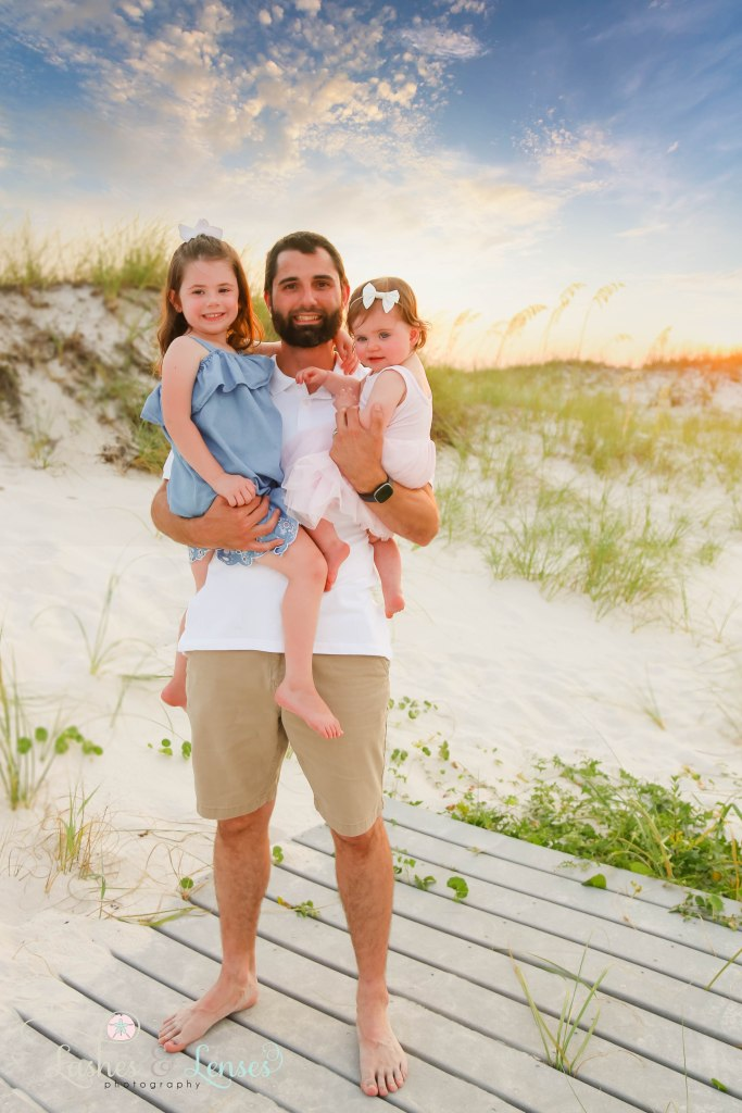 Dad holding his two daughters at Johnsons Beach in Perdido Key Florida