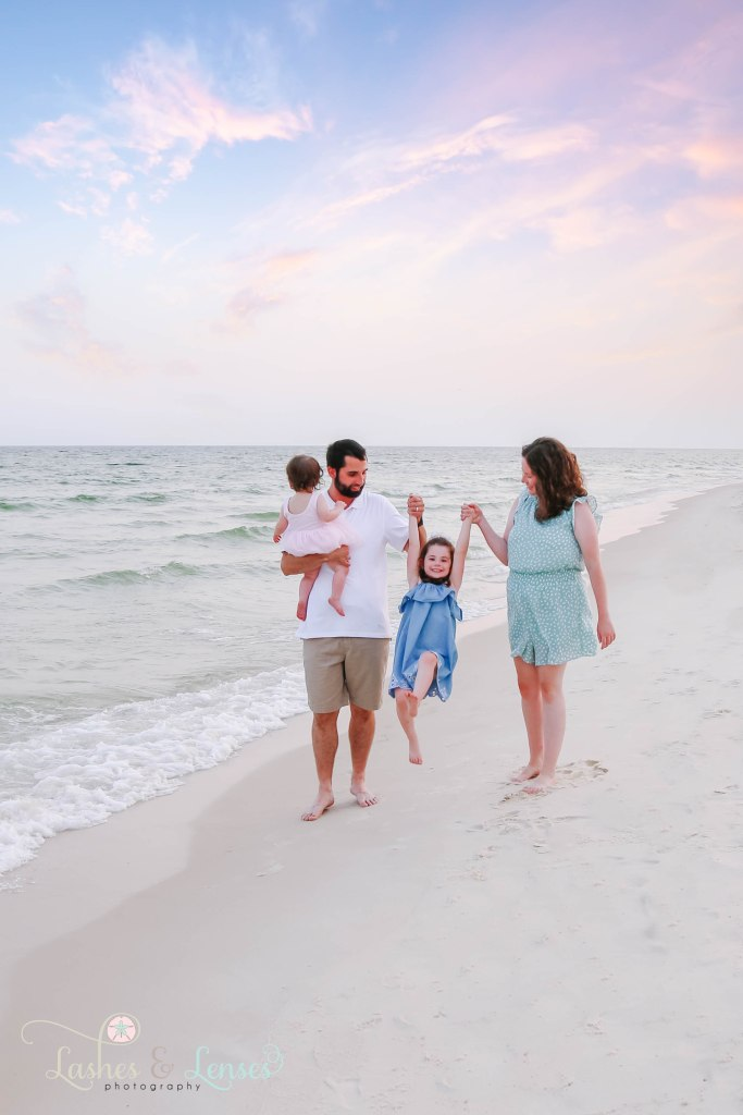Mom and Dad swinging their toddler daughter in between them and dad holding baby girl and walking by the water at Johnsons Beach in Perdido Key Florida