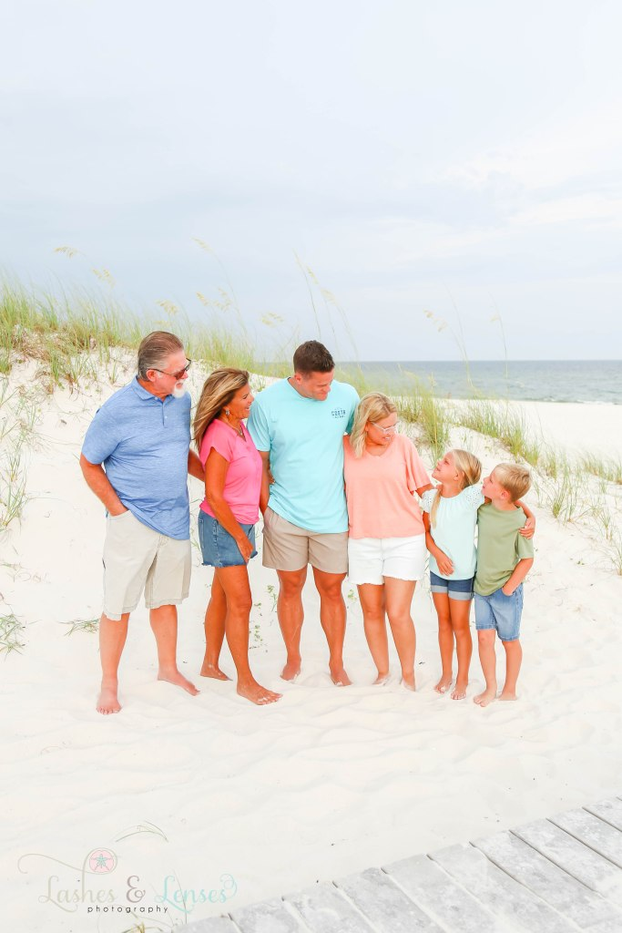 Extended family all looking at the children with the sand dunes behind them at Johnsons Beach in Perdido Key Florida