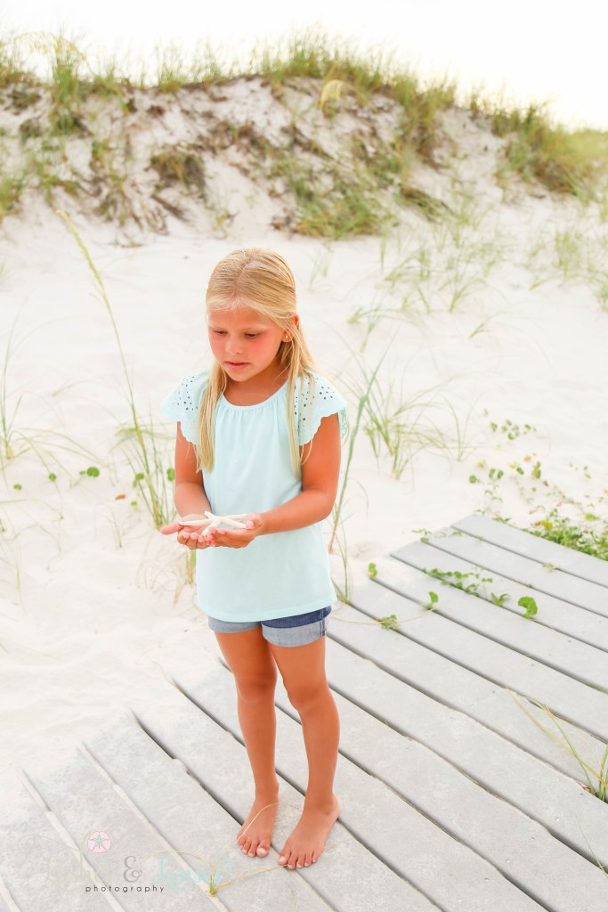 Elementary age girl looking at the starfish in her hands with the sand dunes and sea oats behind her at Johnsons Beach in Perdido Key Florida