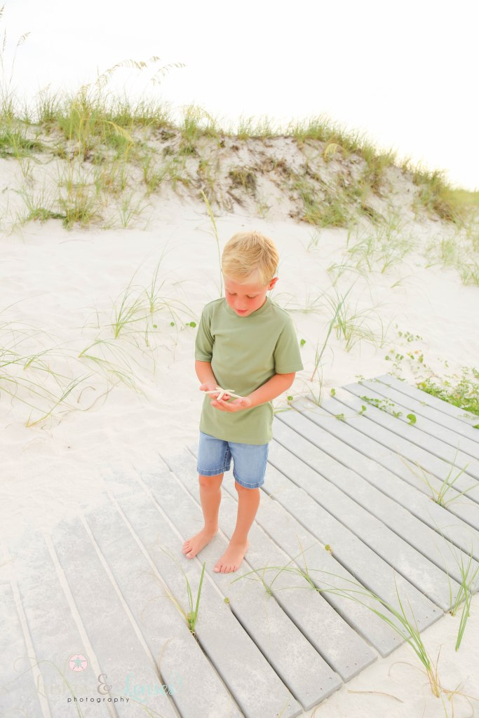 Elementary age boy looking at the starfish in his hands with the sand dunes and sea oats behind him at Johnsons Beach in Perdido Key Florida