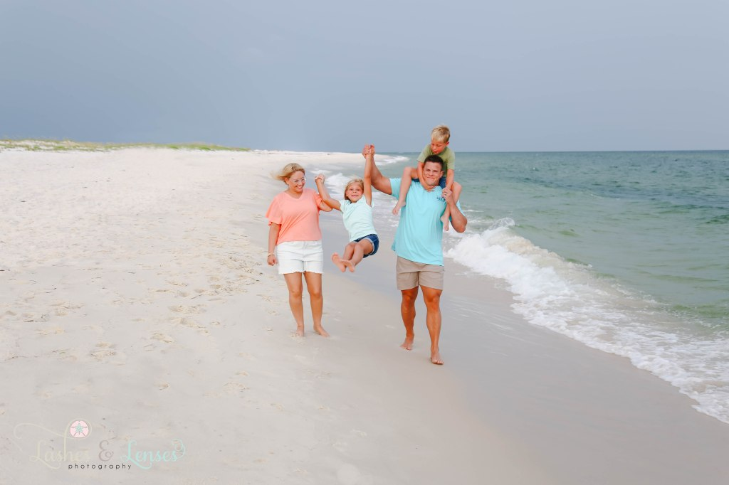 Family walking down by the waters edge, Mom and Dad swinging daughter in between them and son sitting on dads shoulders at Johnsons Beach in Perdido Key Florida
